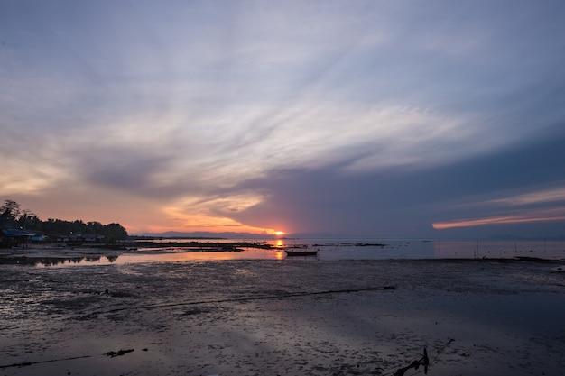 Belo pôr do sol durante a maré baixa na praia da aldeia de koh libong, trang, tailândia