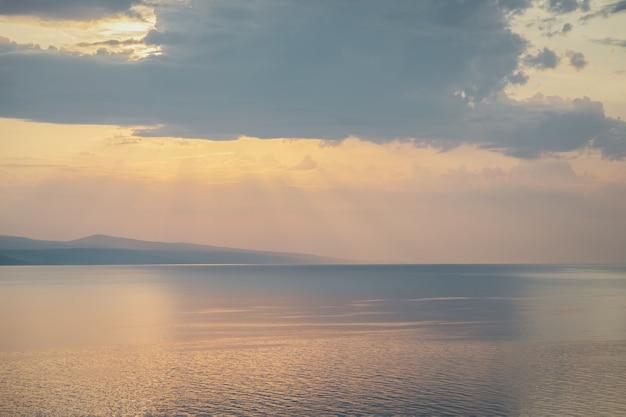Belo pôr do sol em tons pastel na croácia, raios de sol e nuvens cinzentas