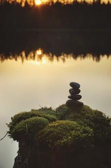 Belo pôr do sol em um lago da floresta, uma pirâmide de pedras em um toco coberto de musgo.