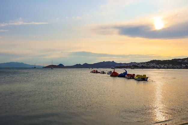 Belo pôr do sol na costa mediterrânea com ilhas e montanhas, barcos e catamarãs