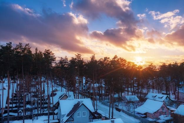Belo pôr do sol na noite de inverno sobre casas com telhados cobertos de neve.