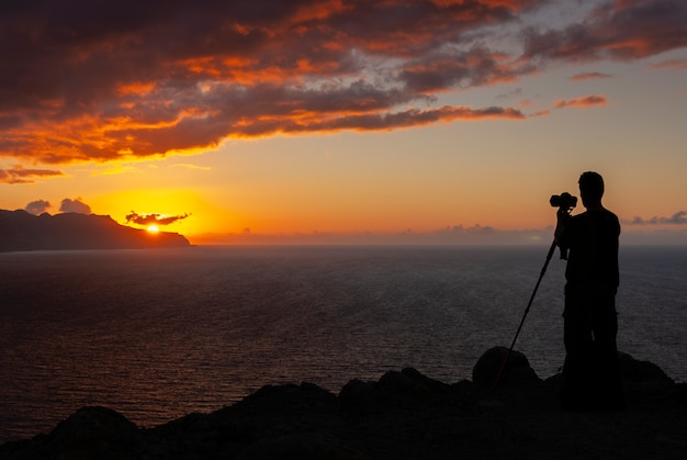 Belo pôr do sol nas falésias com o mar e a silhueta do fotógrafo em primeiro plano, ilha da madeira, portugal