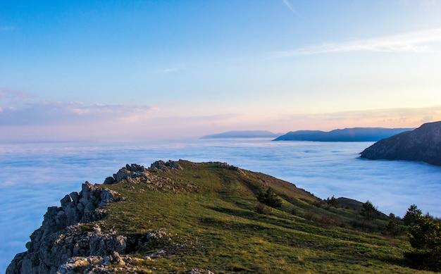 Belo pôr do sol nas montanhas, nuvens baixas coloridas ao pôr do sol.