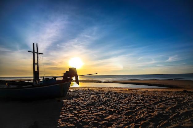 Belo pôr do sol, nascer do sol na praia com barco de silhueta