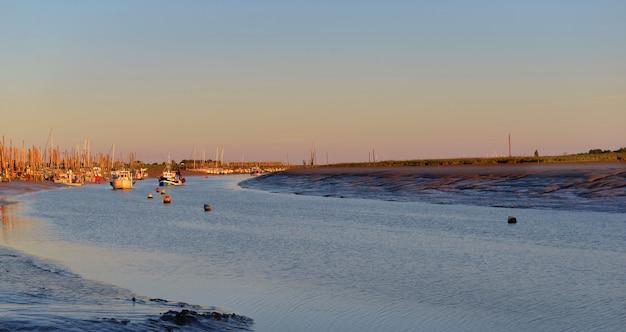 Belo pôr do sol no fairway com fundo de pequenos barcos de pesca na maré baixa
