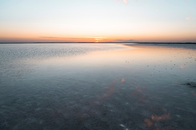 Belo pôr do sol no lago. belo nascer do sol no lago. proteja o meio ambiente. o sol se põe no horizonte rosa e violeta no céu.