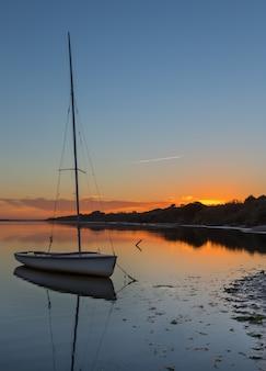 Belo pôr do sol no mar com iate na água. paisagem romântica.