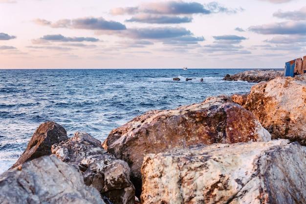 Belo pôr do sol no mar, costa rochosa, bela paisagem