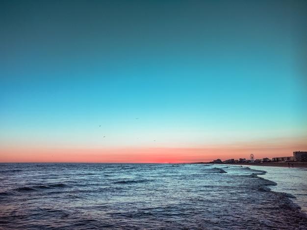 Belo pôr do sol no mar e pequena onda