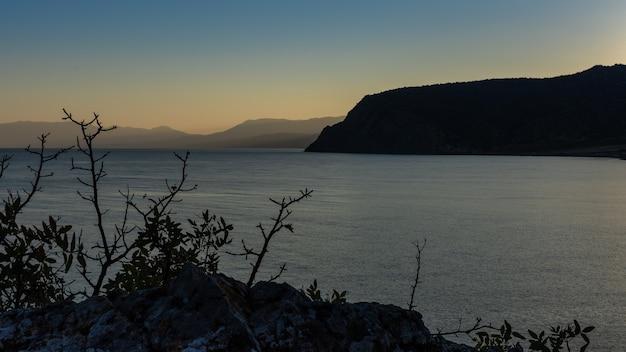 Belo pôr do sol no mar negro, vista das montanhas ao anoitecer, baía de vesele no município de sudak da crimeia