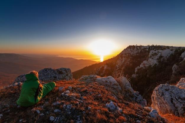Belo pôr do sol no topo da montanha, uma garota turista em um saco de dormir olha as montanhas, reflete, aprecia a vista