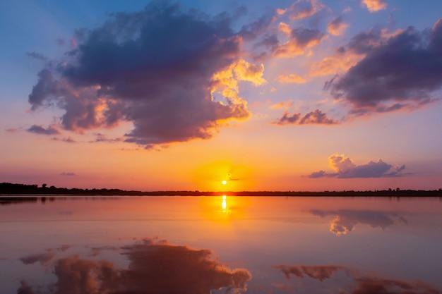 Belo pôr do sol por trás das nuvens e céu azul acima da paisagem sobre a lagoa