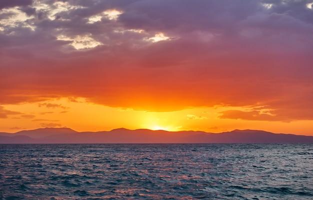Belo pôr do sol sobre o golfo sarônico do mar egeu, na ilha de aegina, grécia - paisagem do pôr do sol - vista do mar