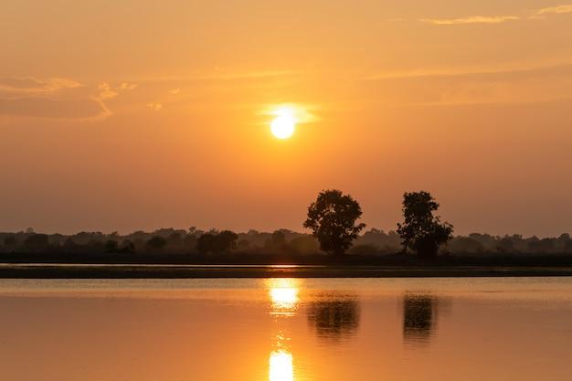 Belo pôr do sol sobre o lago e dois fundo de silhueta de árvore