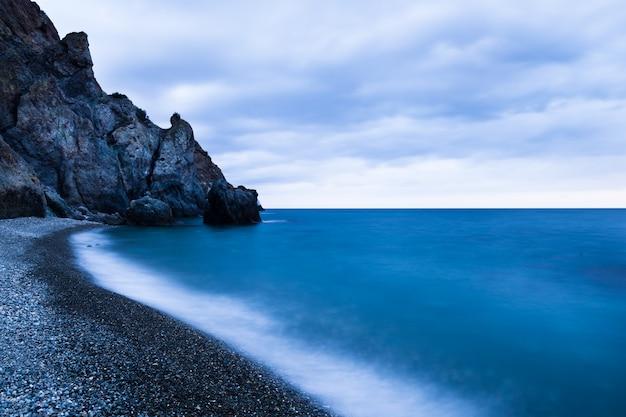 Belo pôr do sol sobre o litoral rochoso tempestuoso do mar negro na crimeia em dia de verão