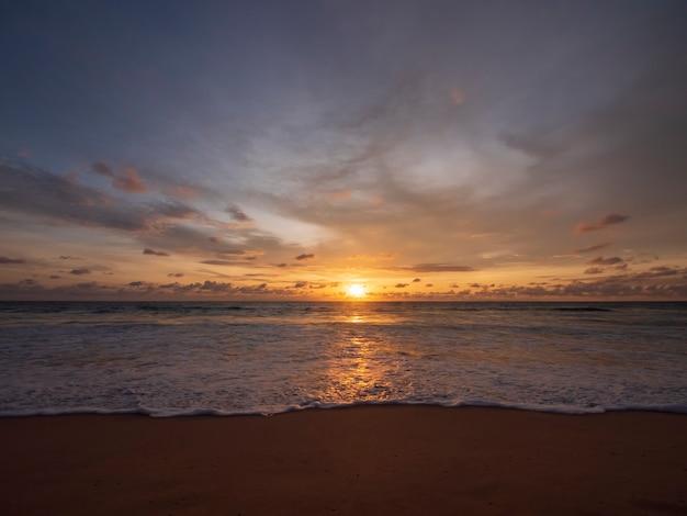 Belo pôr do sol sobre o mar calmo, com fundo de céu de nuvem. pôr do sol sobre a praia tropical. conceito de verão da natureza. pico do sol sobre o mar com luz amarela reflete na água do mar. paisagem tranquila do mar.