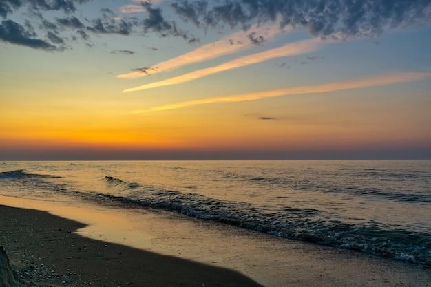 Belo pôr do sol sobre o mar, com reflexo na água, majestosas nuvens no céu