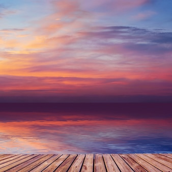 Belo pôr do sol sobre o mar, com reflexo na água.