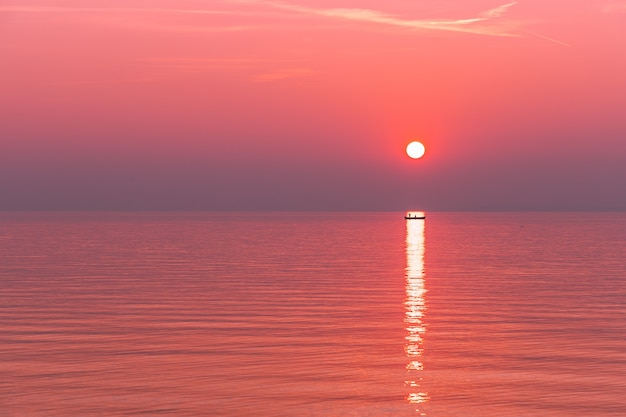 Belo pôr do sol vermelho durante o nevoeiro no lago de garda. nos raios do sol poente é possível ver a silhueta de um barco com pescadores.