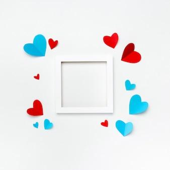 Belo quadro quadrado branco com copyspace para texto em fundo branco, decorado com corações de papel artesanal