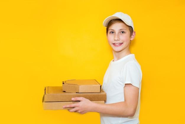 Belo rapaz adolescente com uma pilha de caixas de pizza em um fundo amarelo. trabalho na infância conceito