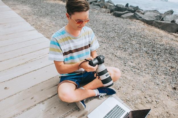 Belo rapaz o fotógrafo a trabalhar com um laptop na praia