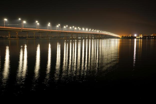 Belo reflexo brilhante de lanternas brilhantes com luz fria no grande rio dnieper sob uma longa ponte que passa sobre ele