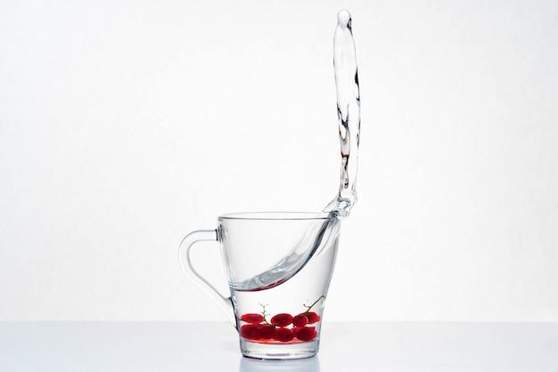 Belo respingo de água em um copo de vidro com bagas na parte inferior