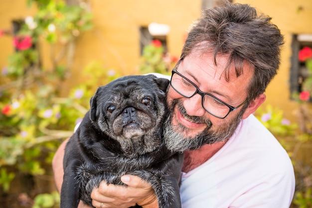 Belo retrato ao ar livre de um homem adulto caucasiano com barba preta e cachorro engraçado da mesma cor.