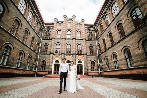 Belo retrato de casal de noivos perto de arquitetura restaurada antiga, prédio antigo, casa velha fora, palácio vintage ao ar livre. amor romântico na rua de atmosfera vintage.