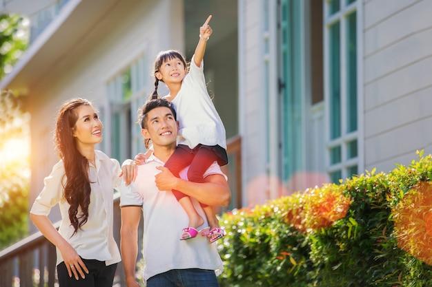 Belo retrato de família sorrindo do lado de fora de sua nova casa