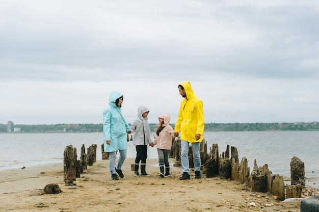 Belo retrato de família, vestido com capa de chuva colorida perto do lago