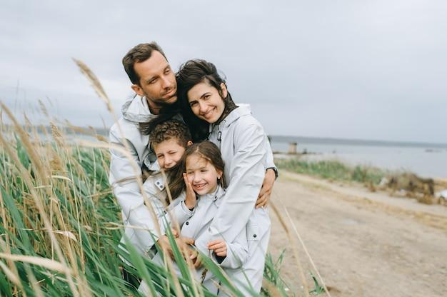 Belo retrato de família, vestido com capa de chuva perto do lago