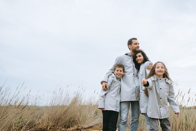 Belo retrato de família vestido com capa de chuva perto do lago