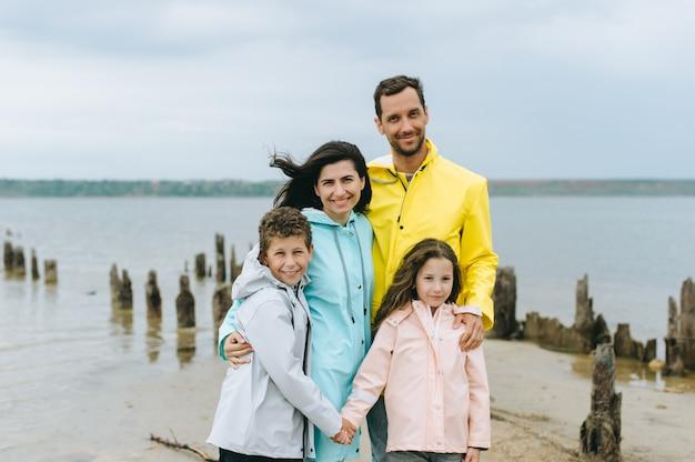 Belo retrato de família vestido com uma capa de chuva colorida perto do lago
