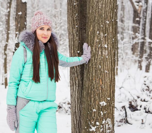 Belo retrato de inverno de mulher jovem no cenário de neve de inverno