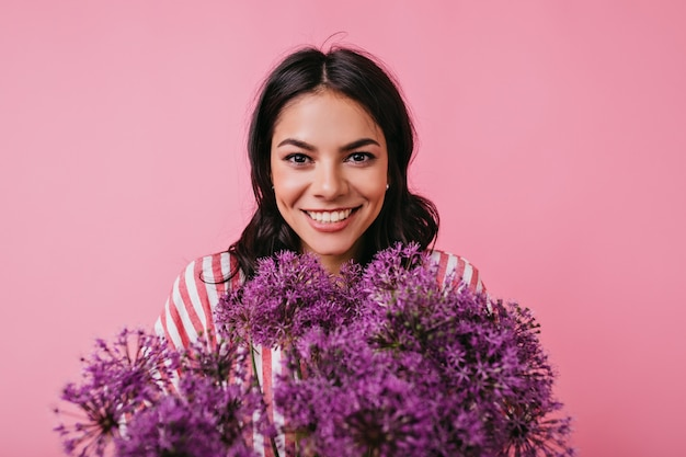Belo retrato de jovem de bom humor com um sorriso sincero. mulher de vestido rosa segurando um enorme buquê de flores.