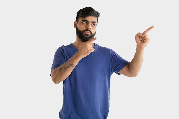 Belo retrato de meio corpo masculino isolado no fundo branco do estúdio. jovem hindu emocional de camisa azul. expressão facial, emoções humanas, conceito de publicidade. apontando e escolhendo.
