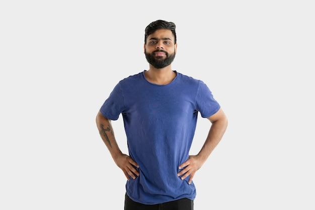 Belo retrato de meio corpo masculino isolado no fundo branco do estúdio. jovem hindu emocional de camisa azul. expressão facial, emoções humanas, conceito de publicidade. de pé e sorrindo.