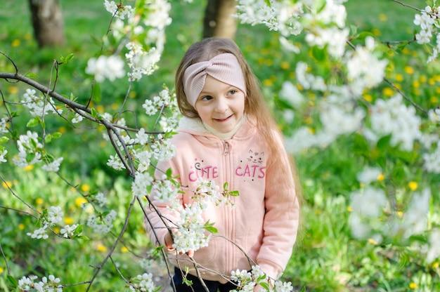 Belo retrato de menina pequena perto de uma árvore de cereja em flor