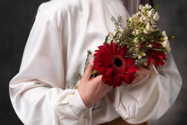 Belo retrato de mulher sênior com flores de perto