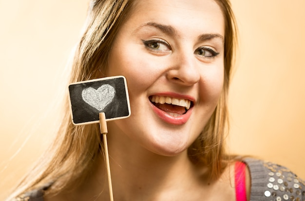 Belo retrato de mulher sorridente posando com giz decorativo javali com coração desenhado