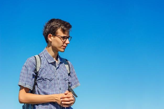 Belo retrato de um jovem com óculos em um fundo de céu azul.