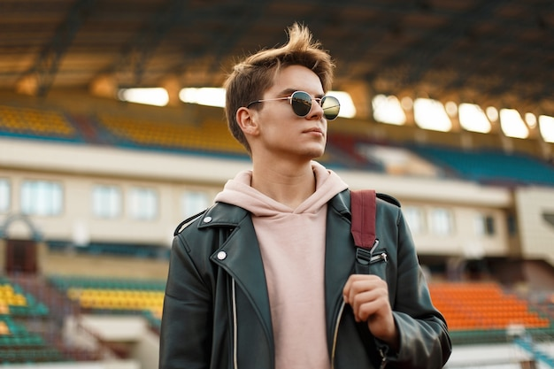 Belo retrato de um jovem esportista com óculos escuros em uma jaqueta preta com uma mochila no estádio