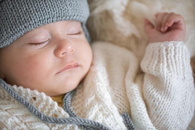 Belo retrato de um menino dormindo com um chapéu de malha quente close-up.