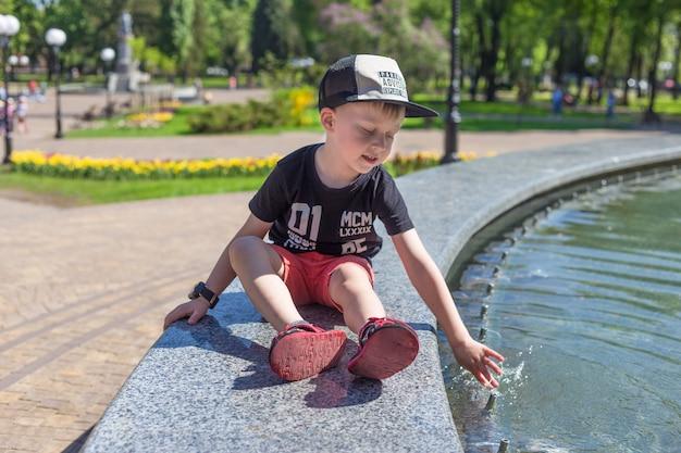 Belo retrato de uma criança perto de uma fonte, em dia quente de verão