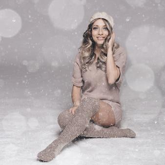 Belo retrato de uma jovem mulher atraente em roupas de malha em fundo nevado