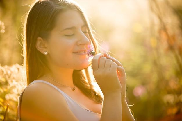 Belo retrato de uma linda mulher cheirando flores em um dia de sol no campo