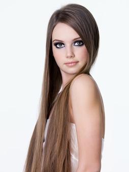Belo retrato de uma menina loira com belos cabelos longos e maquiagem brilhante nos olhos