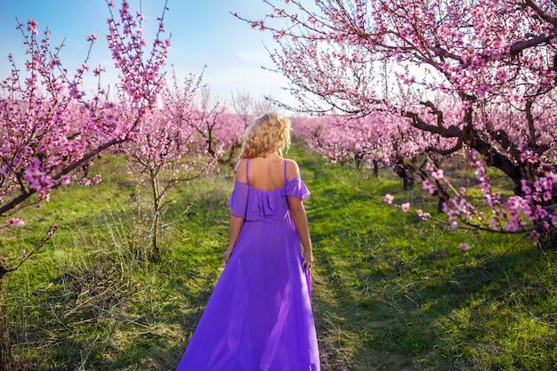 Belo retrato de uma menina na primavera florescendo jardim, dia de sol, jardim de pêssego
